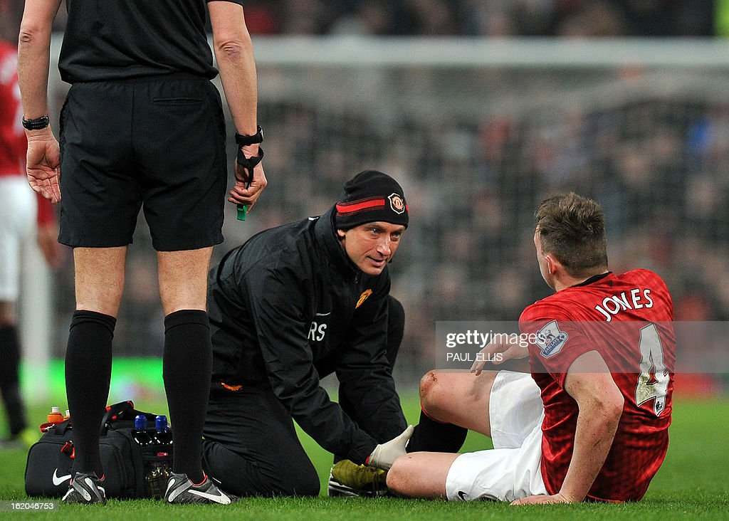 "Manchester United's English defender Phil Jones receives treatment on the field before being substituted during the English FA Cup fifth round football match between Manchester United and Reading at Old Trafford in Manchester, north west England, on February 18, 2013. USE. No use with unauthorized audio, video, data, fixture lists, club/league logos or ""live"" services. Online in-match use limited to 45 images, no video emulation. No use in betting, games or single club/league/player publications."