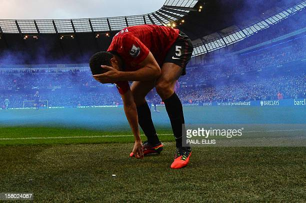 Manchester United's English defender Rio Ferdinand picks up a coin after being struck by an object thrown from the crowd during the English Premier...
