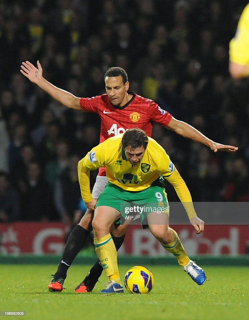"""Manchester United's English defender Rio Ferdinand (L) vies with Norwich City's English striker Grant Holt during the English Premier League football match between Norwich City and Manchester United at Carrow Road stadium in Norwich, England on November 17, 2012. Norwich City won the game 1-0. USE. No use with unauthorized audio, video, data, fixture lists, club/league logos or """"live"""" services. Online in-match use limited to 45 images, no video emulation. No use in betting, games or single club/league/player publications."""