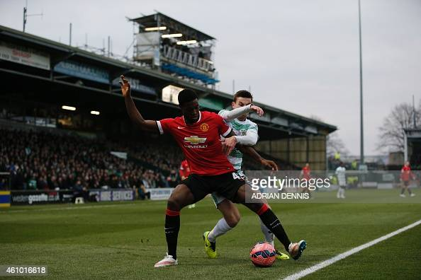Manchester United's English defender Tyler Blackett holds off Yeovil Town's Irish midfielder Kevin Dawson during the English FA Cup third round...