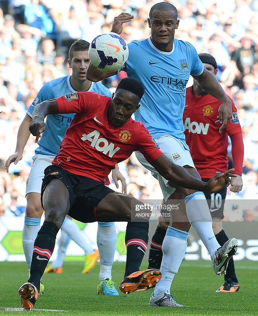 Manchester United's English forward Danny Welbeck (L) vies with Manchester City's Belgian defender Vincent Kompany (R) during the English Premier League football match between Manchester City and Manchester United at the Etihad Stadium in Manchester, northwest England, on September 22, 2013. USE. No use with unauthorized audio, video, data, fixture lists, club/league logos or live services. Online in-match use limited to 45 images, no video emulation. No use in betting, games or single club/league/player publications.