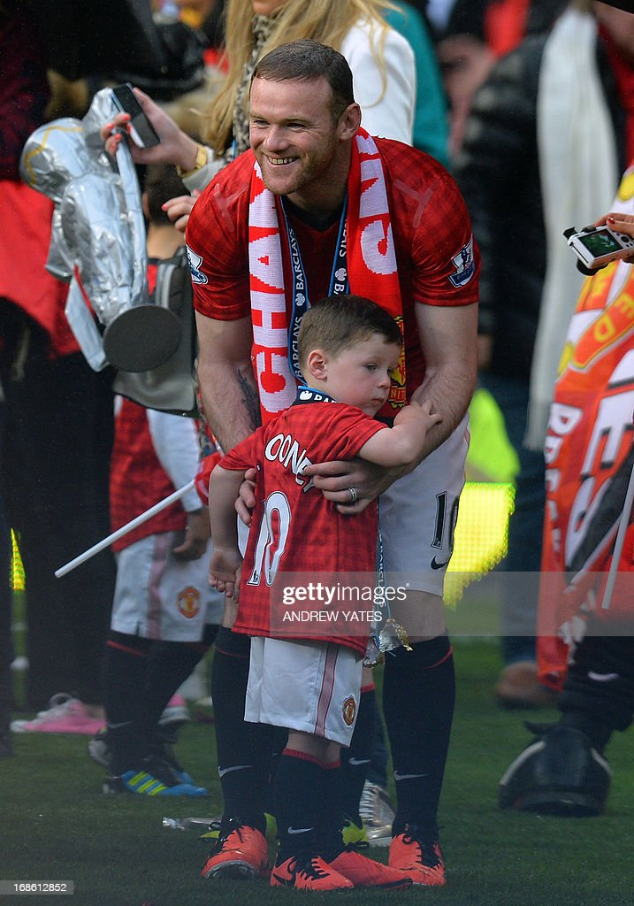 "Manchester United's English forward Wayne Rooney picks up his son Kai during the Premier League championship winners' presentation at the end of the English Premier League football match between Manchester United and Swansea City at Old Trafford in Manchester, northwest England, on May 12, 2013. USE. No use with unauthorized audio, video, data, fixture lists, club/league logos or ""live"" services. Online in-match use limited to 45 images, no video emulation. No use in betting, games or single club/league/player publications"