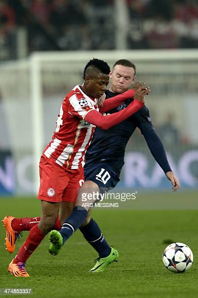 Manchester United's English forward Wayne Rooney vies for the ball with Olympiakos's Nigerian forward Michael Olaitan during the round of 16...