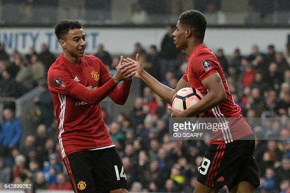 Manchester United's English midfielder Jesse Lingard congratulates Manchester United's English striker Marcus Rashford on scoring their first goal...