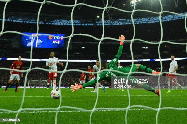 Manchester United's English midfielder Jesse Lingard scores their second goal past Southampton's English goalkeeper Fraser Forster during the English...