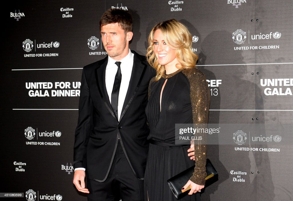Manchester United's English midfielder Michael Carrick (L) and his wife Lisa pose for photographs as they arrive for a gala dinner in aid of UNICEF at Old Trafford in Manchester on November 21, 2013.