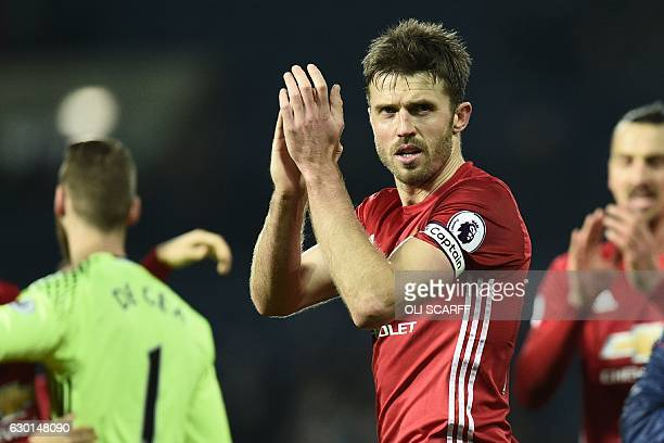 Manchester United's English midfielder Michael Carrick celebrates on the pitch after the English Premier League football match between West Bromwich...