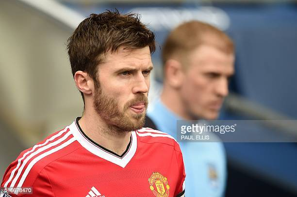 Manchester United's English midfielder Michael Carrick leads his team out onto the pitch during the English Premier League football match between...