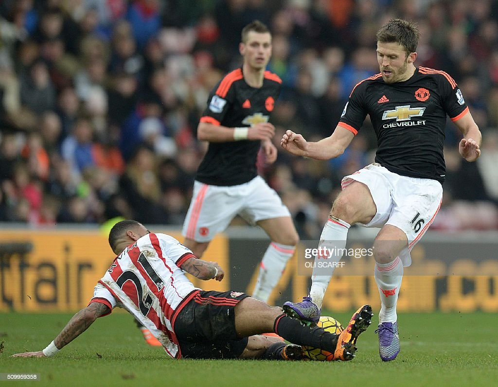 Manchester United's English midfielder Michael Carrick (R) vies with Sunderland's French midfielder Yann M'vila during the English Premier League football match between Sunderland and Manchester United at the Stadium of Light in Sunderland, northeast England on February 13, 2016. Carrick received a yellow card for the challenge. / AFP / OLI SCARFF / RESTRICTED TO EDITORIAL USE. No use with unauthorized audio, video, data, fixture lists, club/league logos or 'live' services. Online in-match use limited to 75 images, no video emulation. No use in betting, games or single club/league/player publications. /