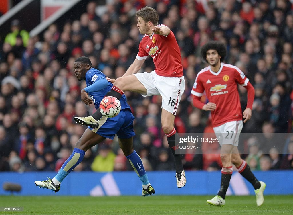 Manchester United's English midfielder Michael Carrick (2L) vies with Leicester City's Ghanaian striker Jeff Schlupp (L) during the English Premier League football match between Manchester United and Leicester City at Old Trafford in Manchester, north west England, on May 1, 2016. / AFP / OLI SCARFF / RESTRICTED TO EDITORIAL USE. No use with unauthorized audio, video, data, fixture lists, club/league logos or 'live' services. Online in-match use limited to 75 images, no video emulation. No use in betting, games or single club/league/player publications. /