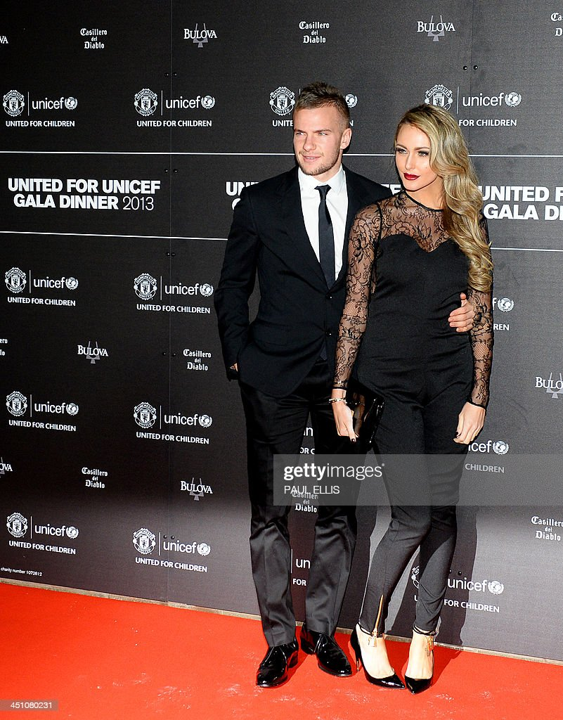 Manchester United's English midfielder Tom Cleverley (L) and partner Georgina Dorsett pose for photographs as they arrive for a gala dinner in aid of UNICEF at Old Trafford in Manchester on November 21, 2013.