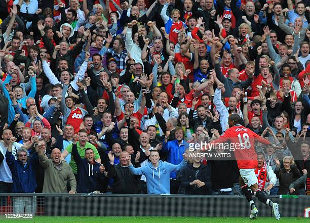 Manchester United's English striker Ashley Young celebrates in front of their supporters after scoring during the English Premier League football...