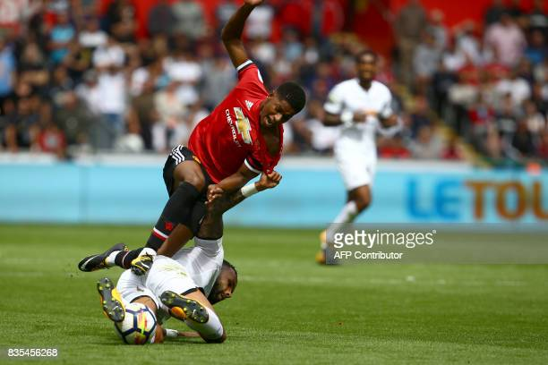 Manchester United's English striker Marcus Rashford and Swansea City's English defender Kyle Bartley collide during the English Premier League...