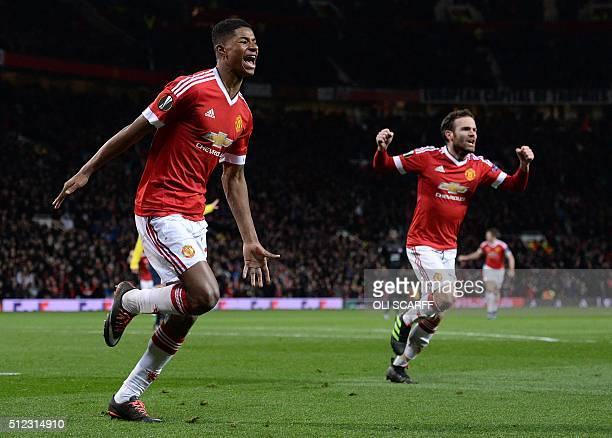 Manchester United's English striker Marcus Rashford celebrates scoring his team's third goal with Manchester United's Spanish midfielder Juan Mata...