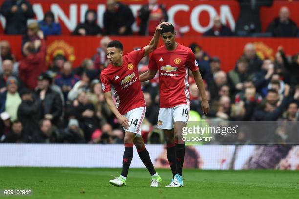 Manchester United's English striker Marcus Rashford celebrates scoring the opening goal with Manchester United's English midfielder Jesse Lingard...