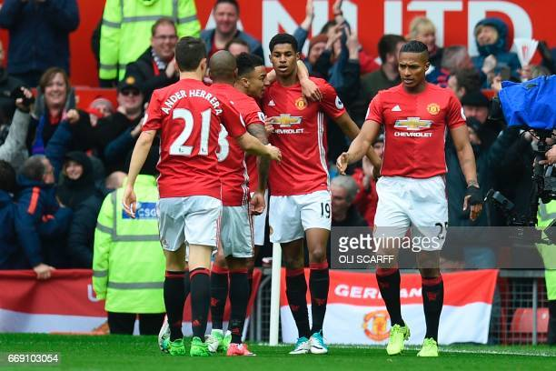 Manchester United's English striker Marcus Rashford celebrates scoring the opening goal with teammates during the English Premier League football...