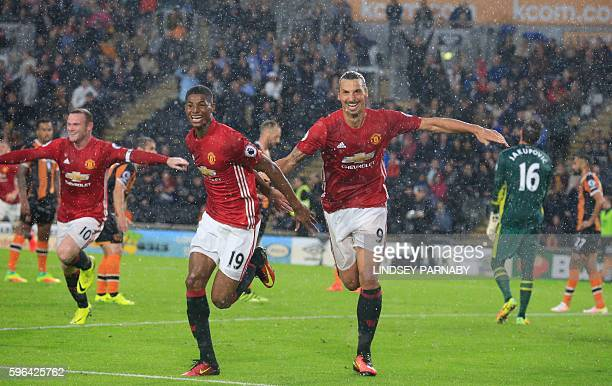 Manchester United's English striker Marcus Rashford celebrates with Manchester United's Swedish striker Zlatan Ibrahimovic after scoring their late...