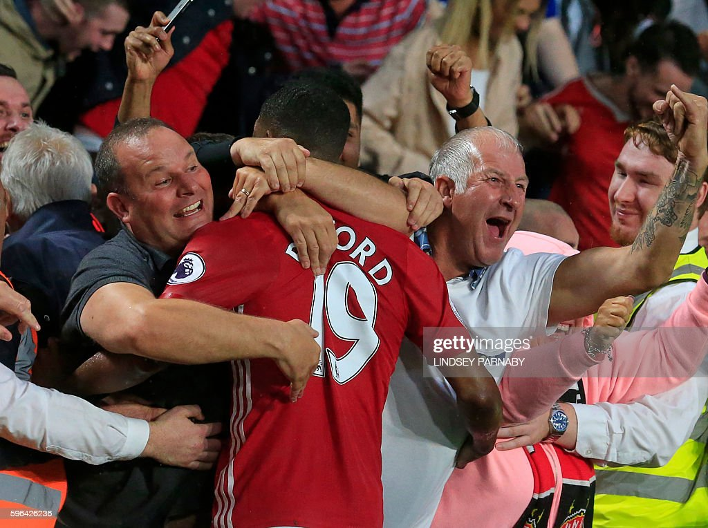 Manchester United's English striker Marcus Rashford celebrates with supporters after scoring their late winning goal during the English Premier League football match between Hull City and Manchester United at the KCOM Stadium in Kingston upon Hull, north east England on August 27, 2016. Manchester united won the game 1-0. / AFP / Lindsey PARNABY / RESTRICTED TO EDITORIAL USE. No use with unauthorized audio, video, data, fixture lists, club/league logos or 'live' services. Online in-match use limited to 75 images, no video emulation. No use in betting, games or single club/league/player publications. /