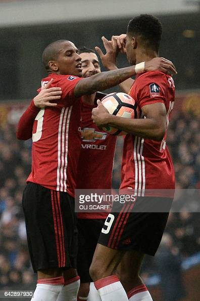 Manchester United's English striker Marcus Rashford celebrates with Manchester United's English midfielder Ashley Young after scoring during the...