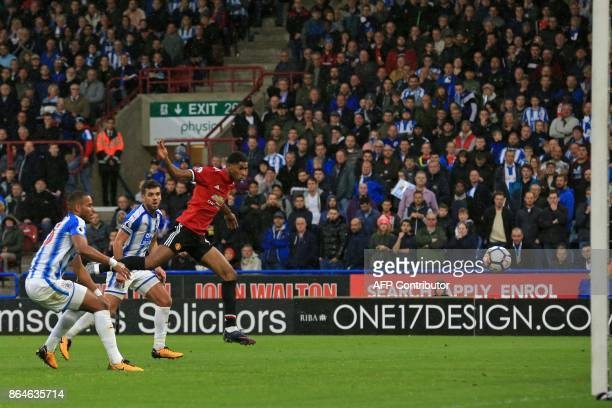 Manchester United's English striker Marcus Rashford heads their first goal during the English Premier League football match between Huddersfield Town...