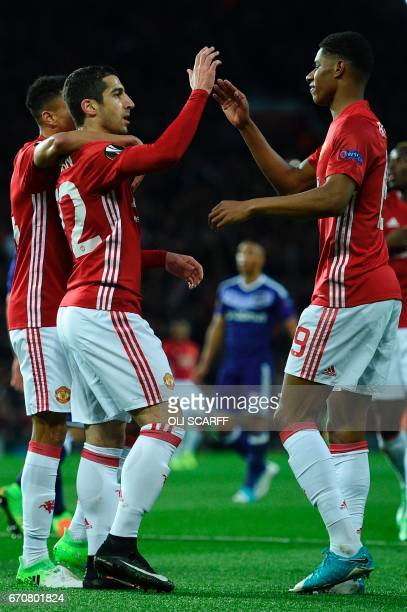 Manchester United's English striker Marcus Rashford high fives Manchester United's Armenian midfielder Henrikh Mkhitaryan after Mkhitaryan's opening...