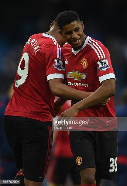 Manchester United's English striker Marcus Rashford hugs Manchester United's French striker Anthony Martial following the English Premier League...