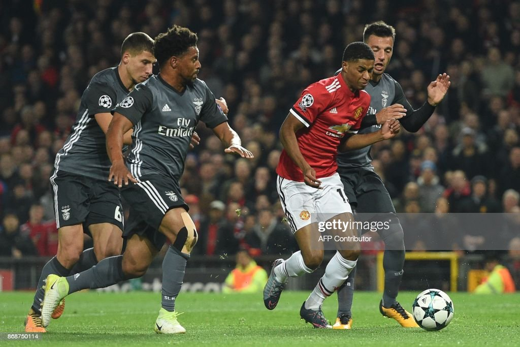 Manchester United's English striker Marcus Rashford (2nd R) is fouled in the penalty area by Benfica's Greek midfielder Andreas Samaris (R) leading to a penalty scored by Manchester United's Dutch midfielder Daley Blind during the UEFA Champions League Group A football match between Manchester United and Benfica at Old Trafford in Manchester, north west England on October 31, 2017. Manchester United won the game 2-0. / AFP PHOTO / Oli SCARFF