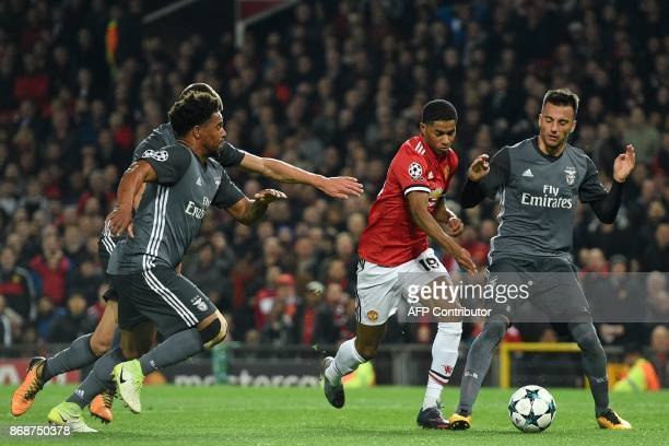 Manchester United's English striker Marcus Rashford is fouled in the penalty area by Benfica's Greek midfielder Andreas Samaris leading to a penalty...