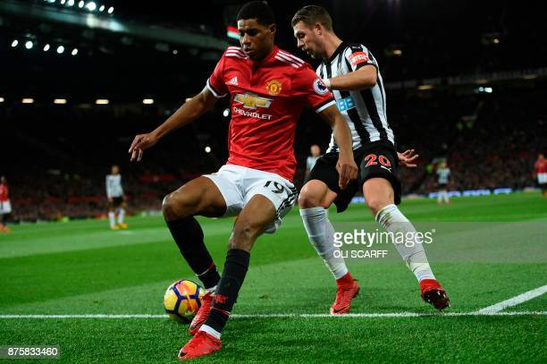 Manchester United's English striker Marcus Rashford is hussled into touch by Newcastle United's French midfiielder Florian Lejeune during the English...