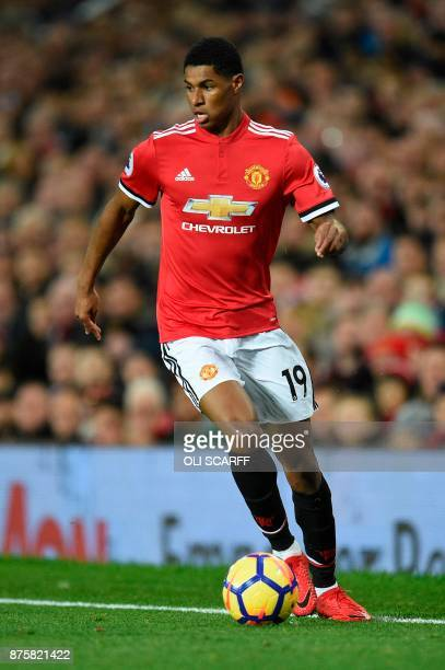 Manchester United's English striker Marcus Rashford runs with the ball during the English Premier League football match between Manchester United and...