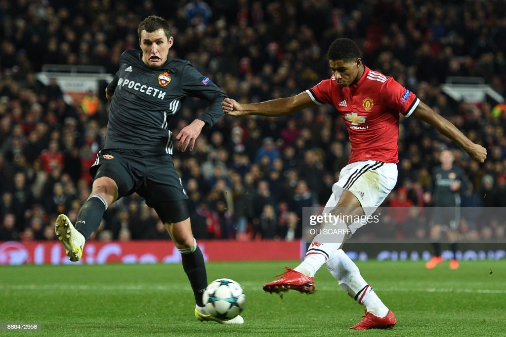 Manchester United's English striker Marcus Rashford (R) shoots under pressure from CSKA Moscow's Russian defender Viktor Vasin (L) to score their second goal during the UEFA Champions League Group A football match between Manchester United and CSKA Moscow at Old Trafford in Manchester, north west England on December 5, 2017. / AFP PHOTO / Oli SCARFF