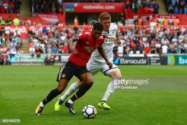 Manchester United's English striker Marcus Rashford vies with Swansea City's English defender Alfie Mawson during the English Premier League football...