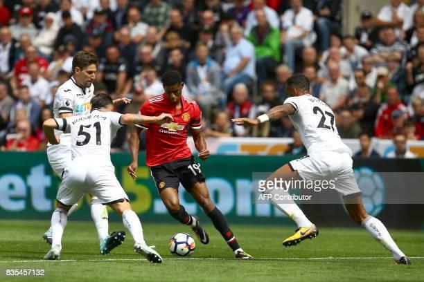 Manchester United's English striker Marcus Rashford vies with Swansea City's Spanish midfielder Roque Mesa and Swansea City's English defender Kyle...