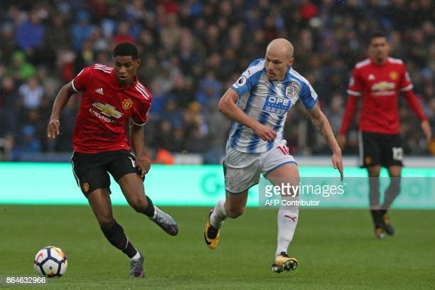Manchester United's English striker Marcus Rashford vies with Huddersfield Town's Australian midfielder Aaron Mooy during the English Premier League...
