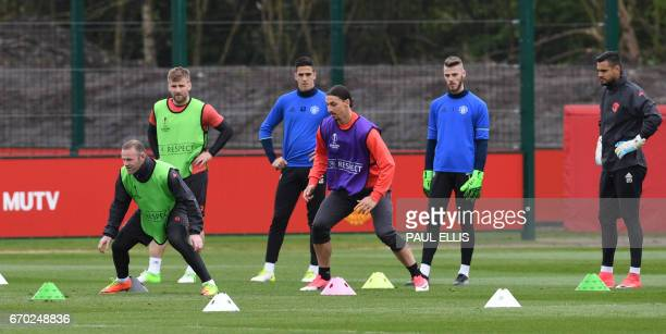 Manchester United's English striker Wayne Rooney and Manchester United's Swedish striker Zlatan Ibrahimovic take part in an exercise as Manchester...