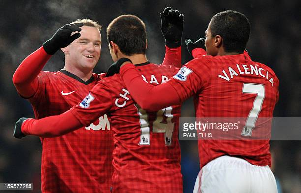 Manchester United's English striker Wayne Rooney celebrates scoring the opening goal with Ecuadorian midfielder Antonio Valencia and Mexican striker...