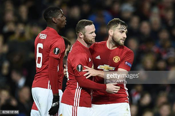 Manchester United's English striker Wayne Rooney celebrates scoring the opening goal with Manchester United's English defender Luke Shaw during the...