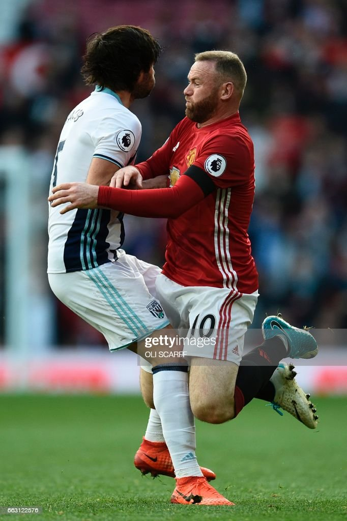 Manchester United's English striker Wayne Rooney (R) collides with West Bromwich Albion's Argentinian midfielder Claudio Yacob (L) during the English Premier League football match between Manchester United and West Bromwich Albion at Old Trafford in Manchester, north west England, on April 1, 2017. / AFP PHOTO / Oli SCARFF / RESTRICTED TO EDITORIAL USE. No use with unauthorized audio, video, data, fixture lists, club/league logos or 'live' services. Online in-match use limited to 75 images, no video emulation. No use in betting, games or single club/league/player publications. /