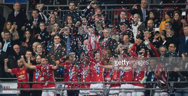Manchester United's English striker Wayne Rooney lifts the trophy as Manchester United players celebrate their victory after the English League Cup...
