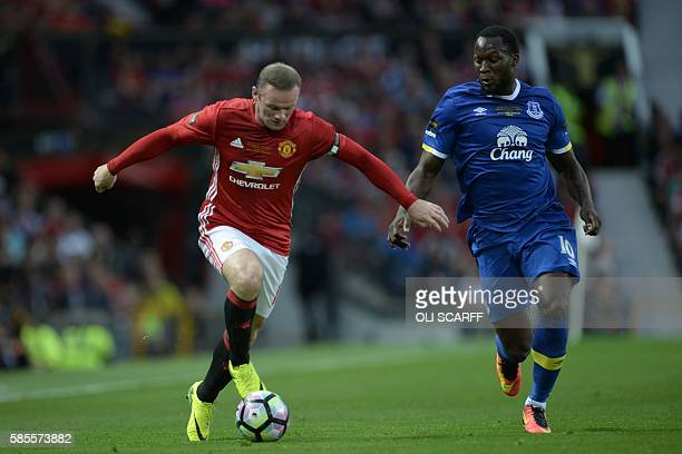 Manchester United's English striker Wayne Rooney runs with the ball challenged by Everton's Belgian striker Romelu Lukaku during the friendly Wayne...
