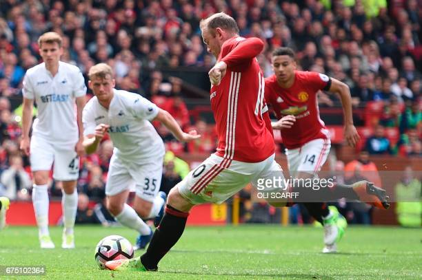 Manchester United's English striker Wayne Rooney scores from the penalty spot for the opening goal during the English Premier League football match...