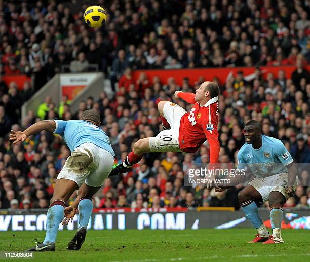 Manchester United's English striker Wayne Rooney scores their second goal between Manchester City's Belgian midfielder Vincent Kompany and English...