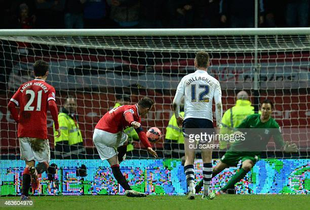 Manchester United's English striker Wayne Rooney scores their third goal from the penalty spot during the FA Cup fifth round football match between...