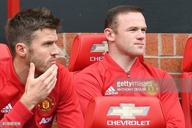 Manchester United's English striker Wayne Rooney sits on the substitutes bench with Manchester United's English midfielder Michael Carrick during the...