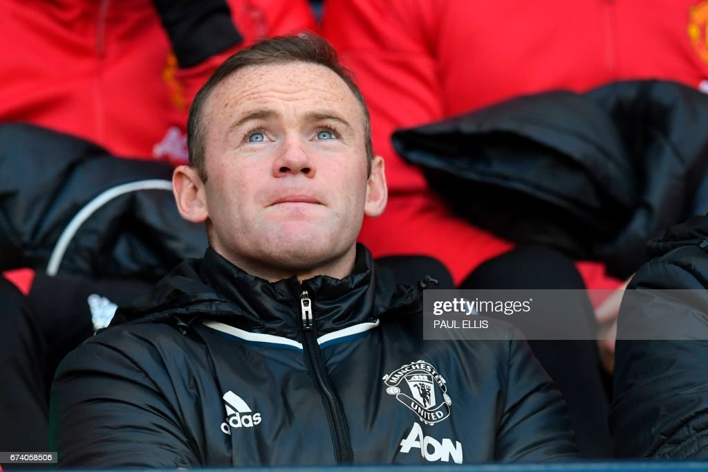 Manchester United's English striker Wayne Rooney sits on the substitutes bench ahead of the English Premier League football match between Manchester City and Manchester United at the Etihad Stadium in Manchester, north west England, on April 27, 2017. / AFP PHOTO / Paul ELLIS / RESTRICTED TO EDITORIAL USE. No use with unauthorized audio, video, data, fixture lists, club/league logos or 'live' services. Online in-match use limited to 75 images, no video emulation. No use in betting, games or single club/league/player publications. /