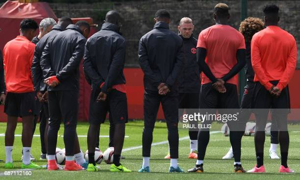 TOPSHOT Manchester United's English striker Wayne Rooney stands with teammates as they observe a minute's silence for the victims of yesterday's...