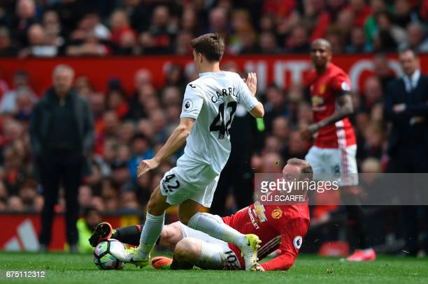 Manchester United's English striker Wayne Rooney tackles Swansea City's English midfielder Tom Carroll during the English Premier League football...