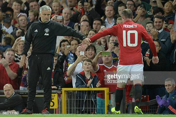 Manchester United's English striker Wayne Rooney touches hands with Manchester United's Portuguese manager Jose Mourinho as he leaves the pitch after...