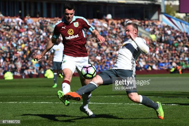 Manchester United's English striker Wayne Rooney vies for the ball with Burnley's English defender Michael Keane during the English Premier League...