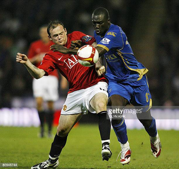Manchester United's English striker Wayne Rooney vies with Portsmouth's Senegalese midfielder Papa Bouba Diop during their Premier League football...